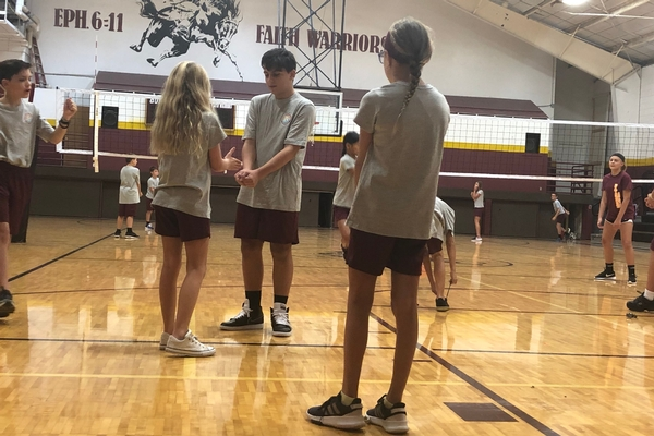 bcs middle students work on volleyball skills in the gym